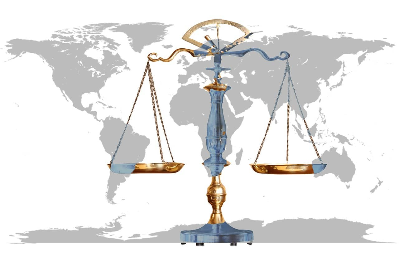 The graphics image depicts the scales of justice against the background of the world map of the continents.